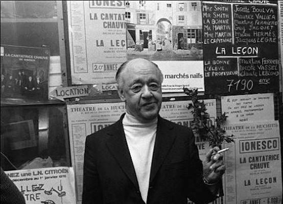 Eugene Ionesco in front of a billboard displaying his works